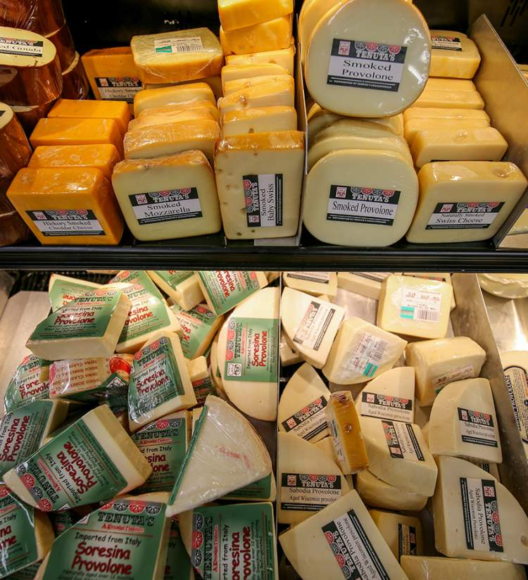 Tenuta's Deli in Kenosha offering an array of different cheeses, including smoked gouda, hickory smoked cheddar, smoked mozzarella, smoked baby swiss, smoked provolone, and naturally smoked swiss cheese.
