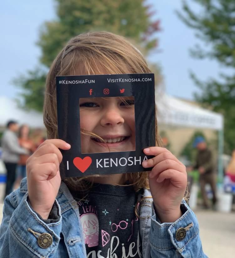 girl holding I Heart Kenosha frame