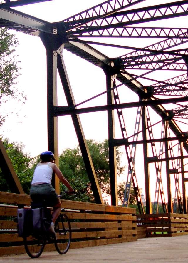 People and Biker Crossing Bridge