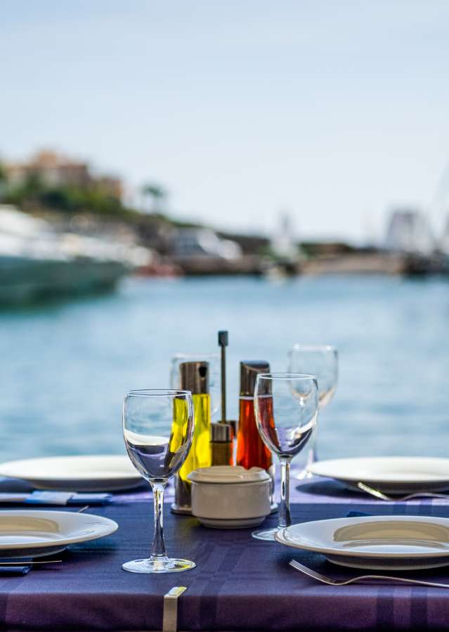 Patio dining table with wine glasses and boats