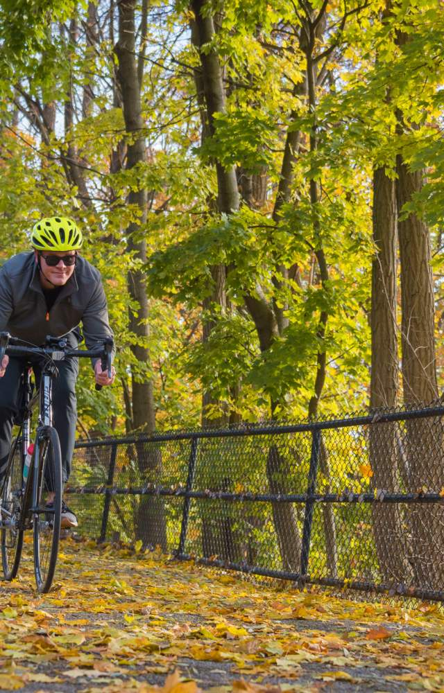 A bicyclist bikes along the East Bank Trail during Autumn