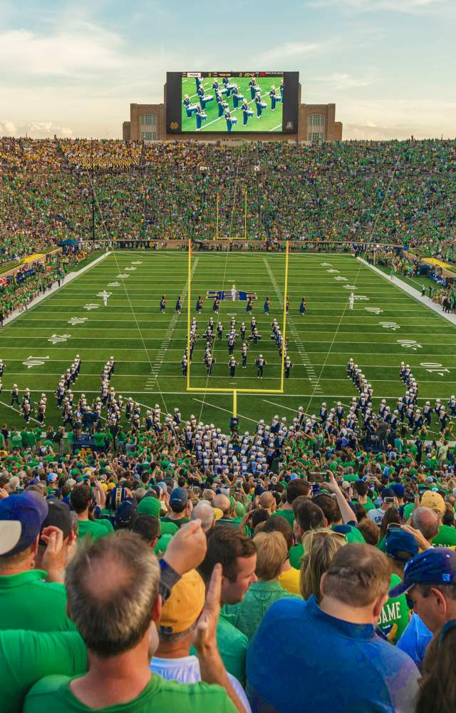 Notre Dame Stadium filled on gameday with the band marching onto the field