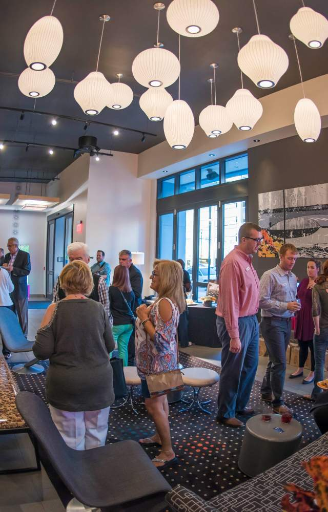 A group of people enjoy a happy hour in the lobby of Aloft South Bend