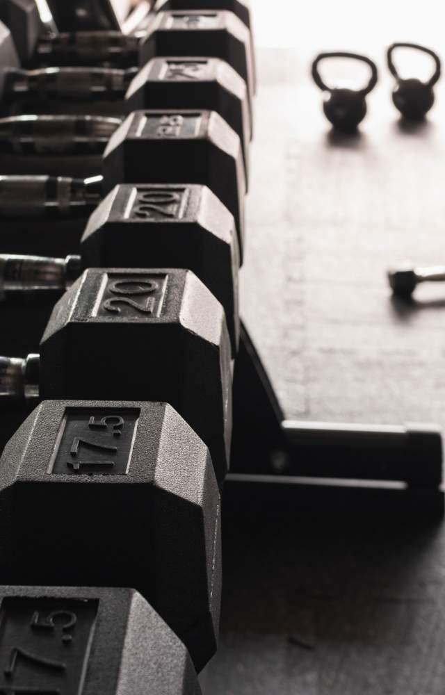 Dumbbells and kettlebells on a gym floor