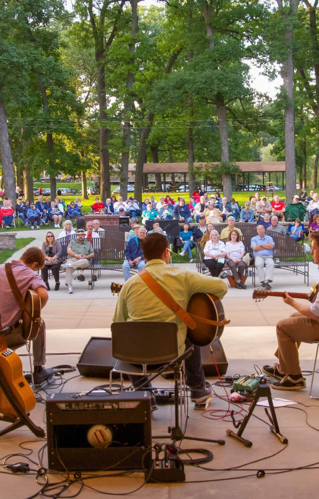 A band play music in front of an audience in a park
