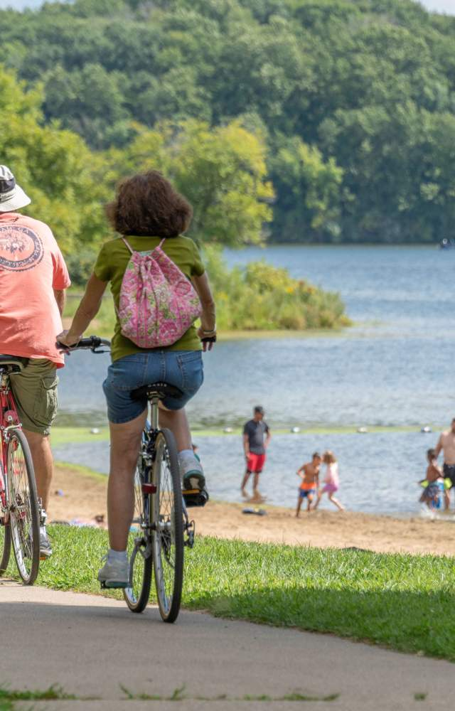 Bicyclists ride past Worster Lake at Potato Creek State Park in North Liberty