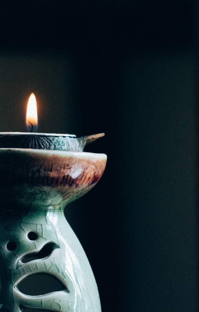 A candle burns in the foreground