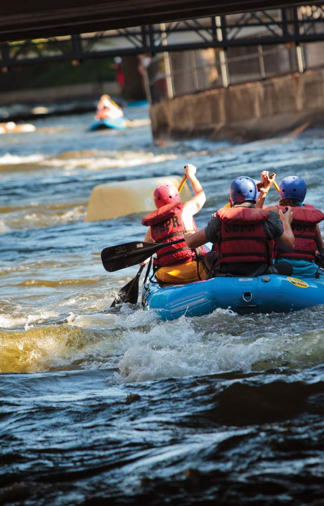 A group of people rafter down the East Race Waterway in the heart of downtown South Bend