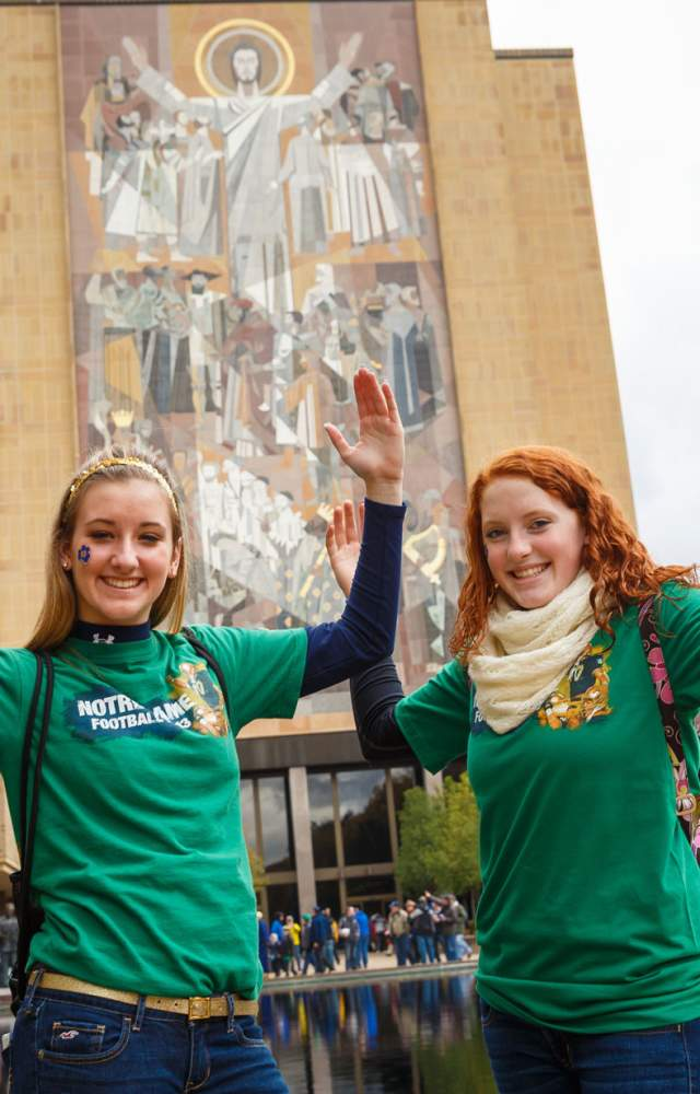 Two girls pose in front of Touchdown Jesus
