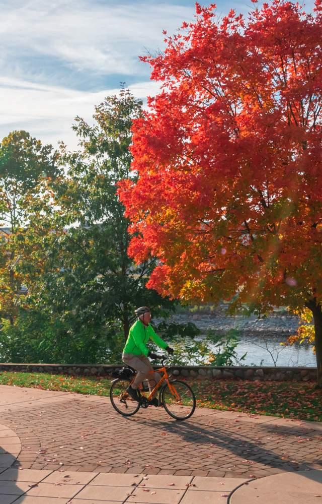 A bicyclist rides along the Mishawaka river walk in Autumn