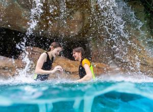 Two girls playing in a waterfall at Discovery Cove