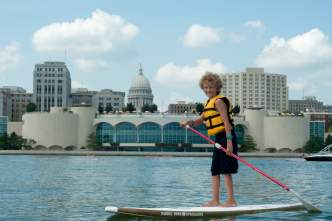 A boy paddleboards on Lake Monona with the Madison skyline behind him