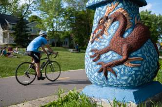 A man bikes past a piece of art off one of Madison's bike paths