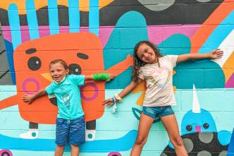 Two kids pose with a colorful mural