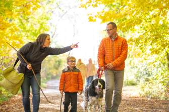 A family takes their dog for a walk through the woods