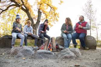A family roasting marshmallows over a campfire at Picnic Point