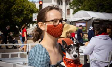 A young woman in a orange mask sits outside at a restaurant with the Wisconsin State Capitol in the background. A small dog wearing an orange bandana is on her lap.