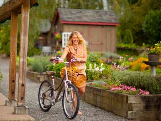 woman in orange dress walks bikes past garden