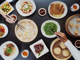 Black wood table full of brightly colored food, and dumplings in wooden baskets, hands reaching across the table with chopsticks