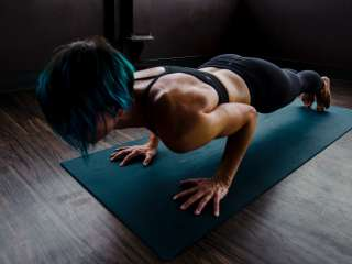 Woman doing push-ups on a teal mat, tan skin, black leggings