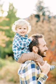 Portrait of young boy on fathers shoulders