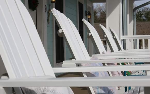 White Lawn Chairs In A Row At Bay Town Inn