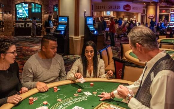 Three people sit at a blackjack table in a casino as a dealer hands out cards.