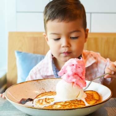 Child eating ice cream on pancakes at The Aussie Grind