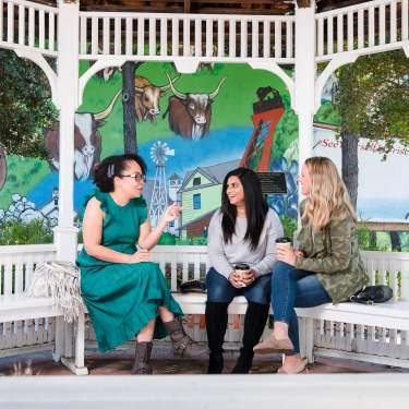 Three women sitting in the Rail District, talking over coffee