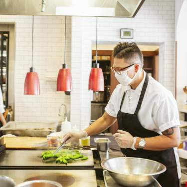 A chef cooks in the kitchen of a restaurant while wearing a mask