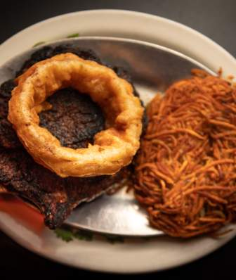 A plate with giant steak and hashbrowns