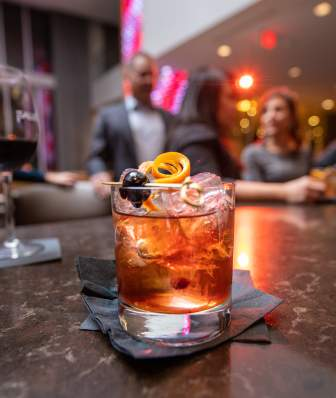 An old fashioned cocktail and a glass of red wine