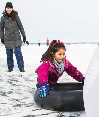 A girl slides on a tube into inflatable bowling pins on frozen Lake Mendota