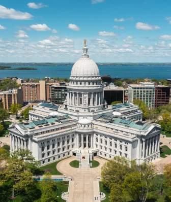 Aerial shot of the Wisconsin State Capitol building. Blue skies are overhead and a lake sits at the back of the photo.