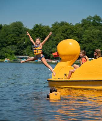 A girl jumps off a duck pedal boat into the water