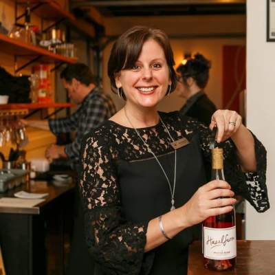 Julie Dalrymple smiles with a bottle of Hazelfern rosé at an upscale event
