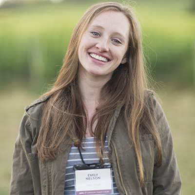 Emily Nelson smiles, sporting an Oregon Pinot Camp nametag, in front of a vineyard.