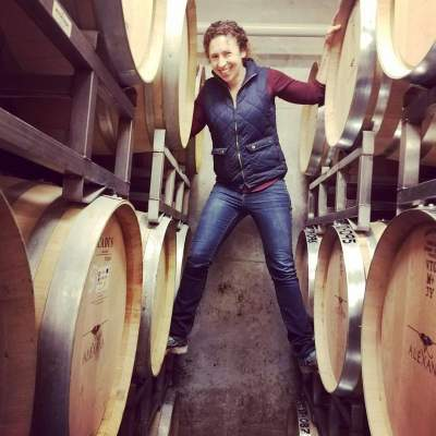 Julia Burke smiles while balancing on barrels in a wine cellar.