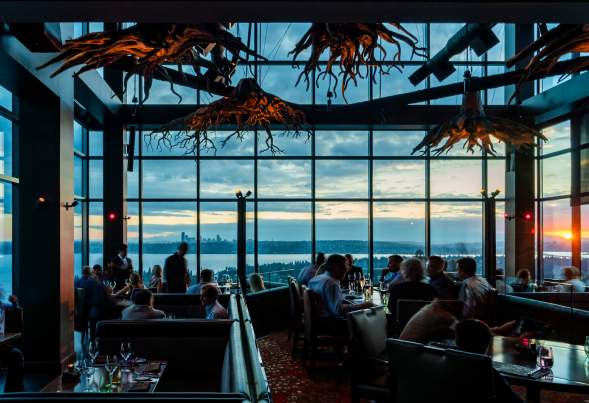 Beautiful chandlers inspired by tree roots set the scene of an expansive dining room of the rooftop restaurant overlooking Lake Washington and Seattle