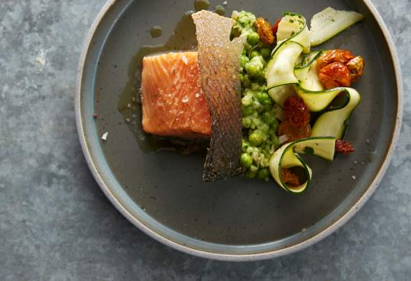 Beautifully plated salmon, with green veggies and a sauce