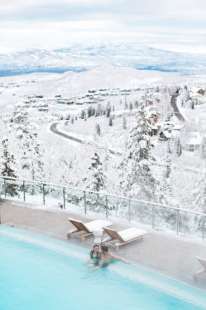 couple in pool in winter with snowy mountains in background