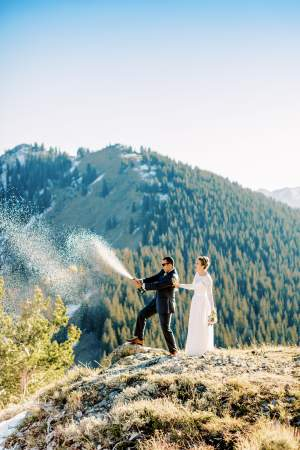 Bride and Groom spray sparkling wine from the top of a mountain