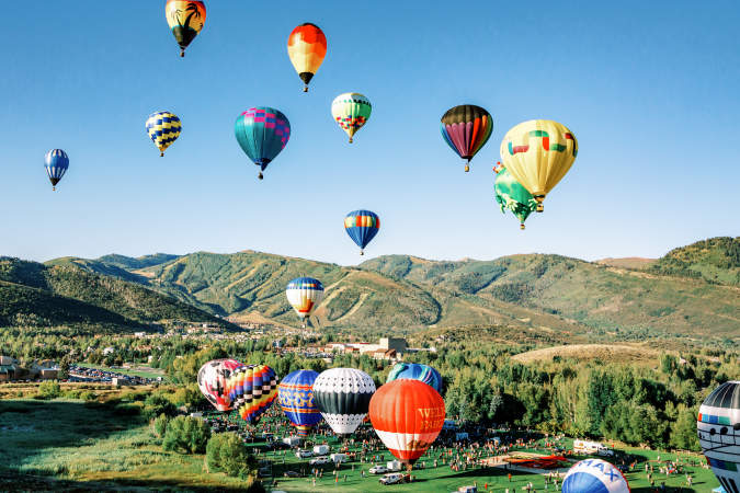 Group of Hot air balloons with scenic mountains in background