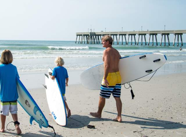 Family surfing on Wrightsville Beach