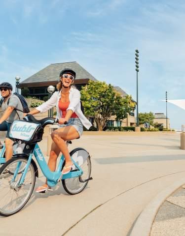 Couple Riding Biking in Milwaukee in Front of Milwaukee Art Museum.