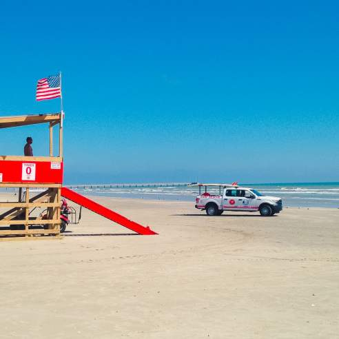 On the beach, a wooden lifeguard tower is painted red across the middle and stairs. Several flags fly from the tower, and a white rescue truck sits near the tower.