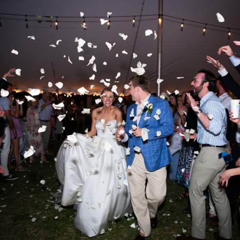 Bride and groom at night reception run toward the camera as white rose petals are thrown at them
