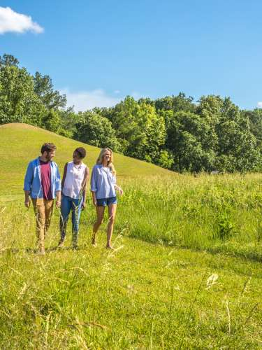 A Man, A Boy and A Woman Walking Down A Grassy Path In Ocmulgee Mounds