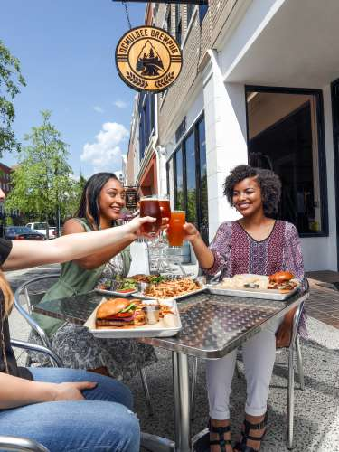 A group toasts to friendship over a meal on the patio at Ocmulgee Brewpub in Macon.