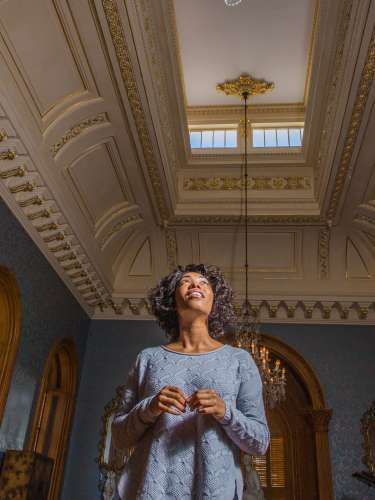 A woman looks at the details on the ceiling inside of the Hay House in Macon, GA